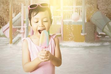 Cheerful kid holds ice cream at pool
