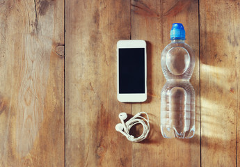fitness concept with bottle of water, mobile phone