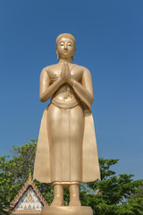 the gold monk statue standing  and greeting