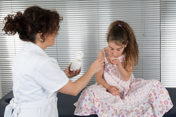 Young girl receiving pill at the hospital