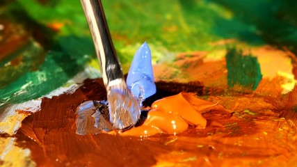Painter mix brown, blue and orange colors oil painting on