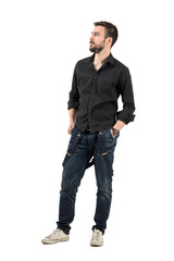 Serious young man with hands in pocket looking up