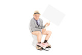Senior holding a blank signboard seated on toilet