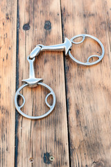 Steel horse snaffle-bit on wooden background.