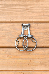 Steel horse snaffle-bit hanging on wooden background.