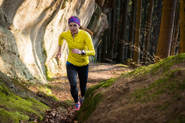 Woman running in the forrest with rocks