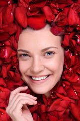 Beautiful happy woman lying in roses