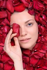 Beautiful happy woman lying in petal of roses