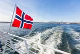 Fototapety Norwegian flag waving on poop of a boat in Oslo