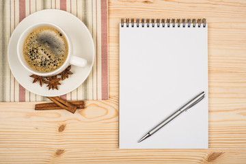 cup of coffee notebook and pen on the wooden table.