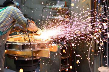 Arbeiter in d. Schwerindustrie flext Werkstück