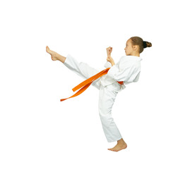 A girl with a red belt makes high kick karate