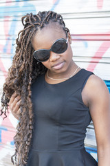 Urban portrait of beautiful african woman with sunglasses.