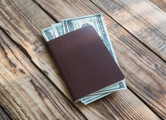 Blank passport with US dollars on wood table