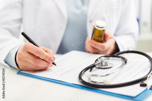 Female doctor filling medical form holding medicine bottle плакат