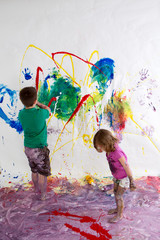 Young brother and sister painting together