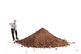 Cheerful young man shoveling a big pile of dirt