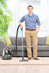 Young man posing with a vacuum cleaner