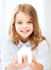 girl holding white paper house