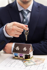 Young businessman broker offering house for rent holding keyring