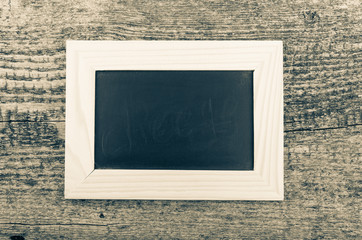 Black chalk board in a light wooden frame on the old wooden tabl