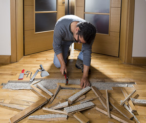 Manual worker disassembling wooden floor ruined from moisture