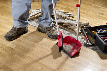 An unrecognizable person with a broom sweeping floor.