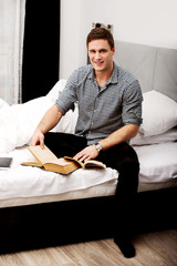 Man with a book in his bed.