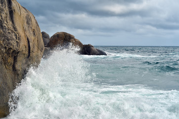 Wave crashing against stones at the rocky beach