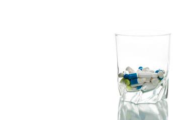 Wasserglas mit Tabletten gefüllt