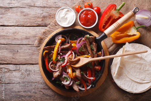 Poster Mexican fajitas on a table. horizontal top view