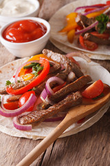 Mexican food: tortilla with meat and vegetables. vertical