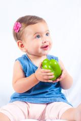 Baby mit grüner Paprika in der Hand