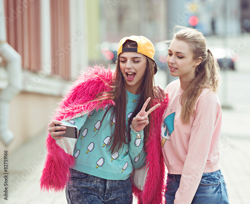 Hipster girlfriends taking a selfie in urban city context - - 82759166