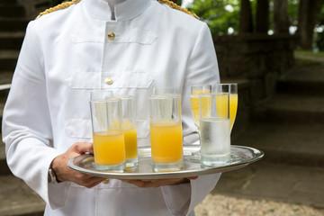 Cameriere in divisa bianca con vassoio e bicchieri