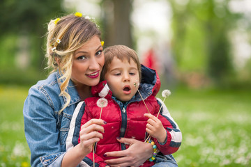 Portrait of playful family blowing dandelions in a park