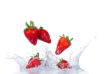 Fresh strawberries in water splash on white