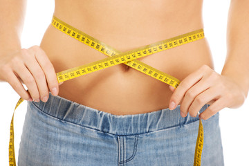 Slim woman measuring her waist.