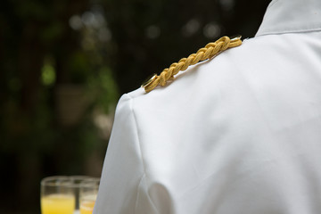 cameriere al lavoro particolare della spalla con decoro dorato