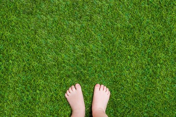 Baby legs standing  on green summer grass