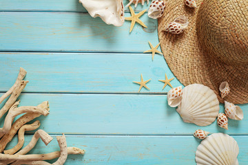summer hat and seashells on wooden background