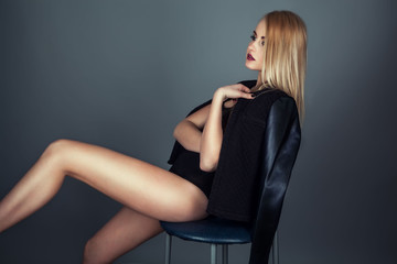 Beautiful blond woman in black leather jacket sitting on chair