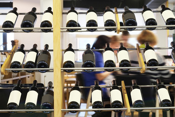Bottles of red wine on a wooden shelf in the restaurant