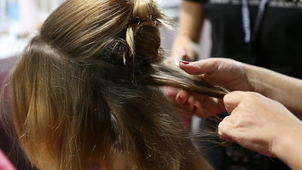 Hairdresser doing fashion model's hair before a fashion show