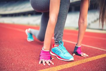 Fitness athlete on track starting blocks preparing for a sprint