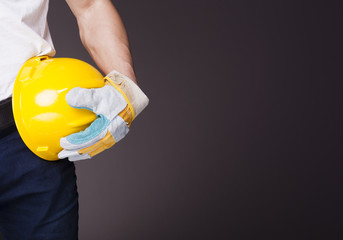 Image of a worker holding a helmet against grey background