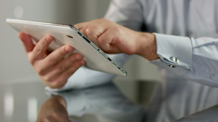 Businessman hands scrolling news feed on tablet PC touchscreen