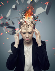 Attractive businesswoman with exploding headache