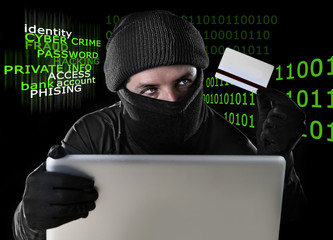 hacker man with credit card and computer in  cyber crime concept