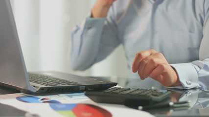 Sales manager calls client, calculates, inserts data on laptop